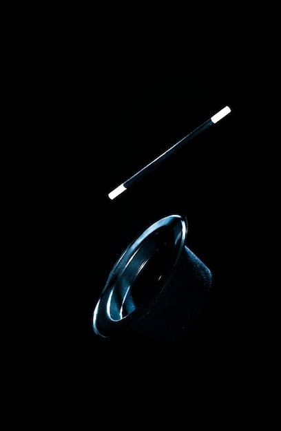 Top black hat and magic wand in air against black background Free Photo