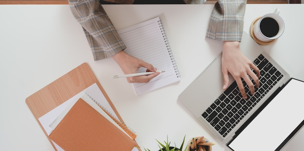 Top  of businesswoman typing on laptop computer and writing her idea Premium Photo