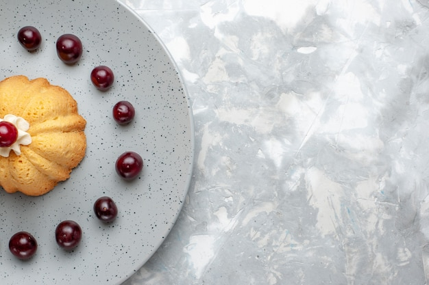 灰色のライトデスクにさくらんぼとトップクローズビューケーキ、ケーキビスケットクリームフルーツの写真 無料写真