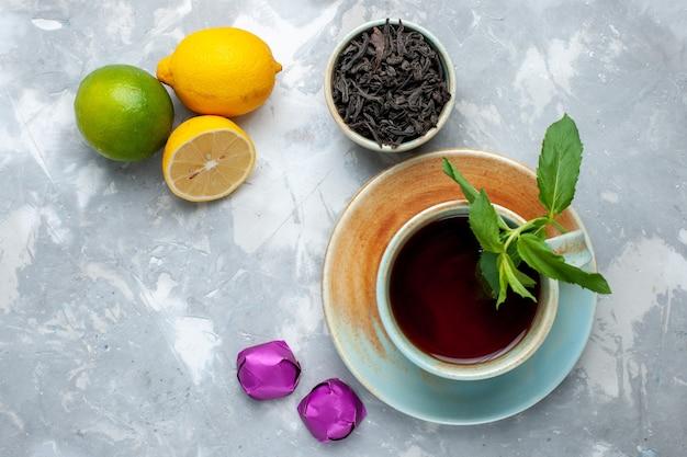 トップクローズアップビューカップティーフレッシュレモンキャンディーとライトテーブル、紅茶フルーツシトラス色の乾燥茶 無料写真