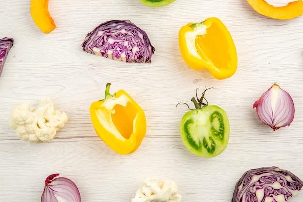 Top vista ravvicinata tagliare le verdure cavolo rosso pomodoro verde zucca cipolla rossa peperone giallo cavolfiore su superficie bianca Foto Gratuite