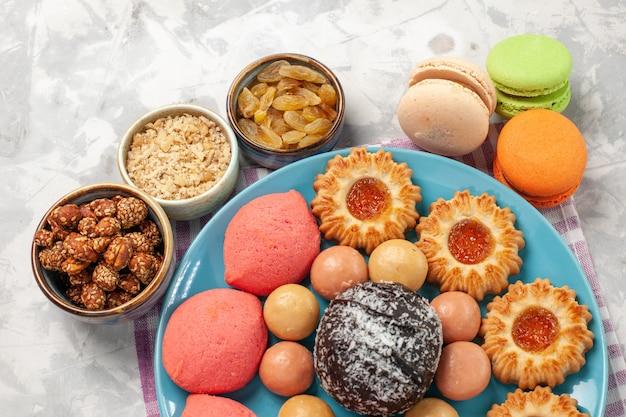 白い机の上にクッキーとマカロンとトップクローズビューおいしいケーキ 無料写真