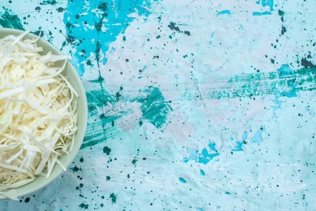 Vista ravvicinata superiore di cavoli affettati freschi all'interno del piatto rotondo su insalata sana di cibo vegetale blu brillante Foto Gratuite