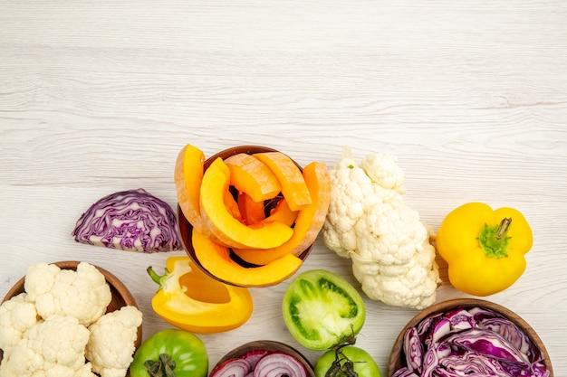 Vista dall'alto ravvicinata verdure fresche tagliate pomodori verdi tagliati cavolo rosso tagliata cipolla tagliata zucca tagliata cavolfiore peperone tagliato in ciotole sulla superficie Foto Gratuite