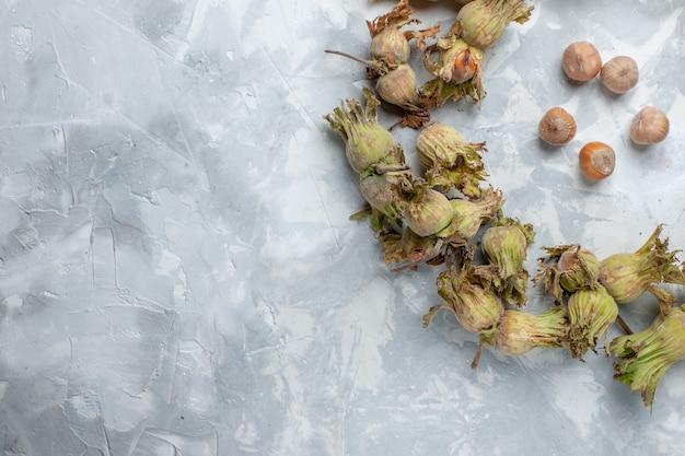 Top vista ravvicinata fresche intere nocciole con bucce su scrivania bianca dado nocciola noce albero pianta Foto Gratuite