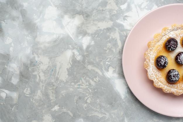 ライトでプレートの内側にさくらんぼが付いている小さなおいしいケーキの上面拡大図 無料写真