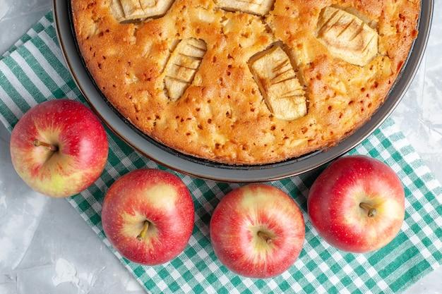 Top vista ravvicinata yummy torta di mele dolce al forno all'interno della padella con le mele sulla scrivania bianca torta torta biscotto zucchero dolce cuocere Foto Gratuite