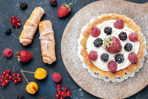Вид сверху на вкусный маленький торт с сахарной пудрой и ягодами вместе с браслетами на темном столе Бесплатные Фотографии
