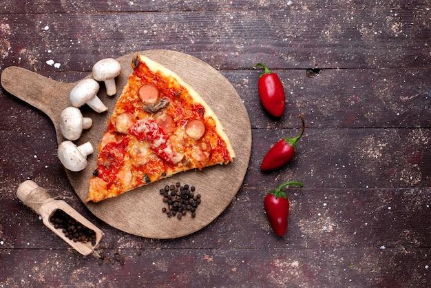 Вид сверху на вкусный кусок пиццы со свежими грибами, помидорами, красным перцем на коричневом столе Бесплатные Фотографии