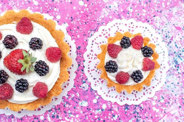ライトホワイトにさまざまなベリーの小さなクリーミーなケーキの上面拡大図 無料写真