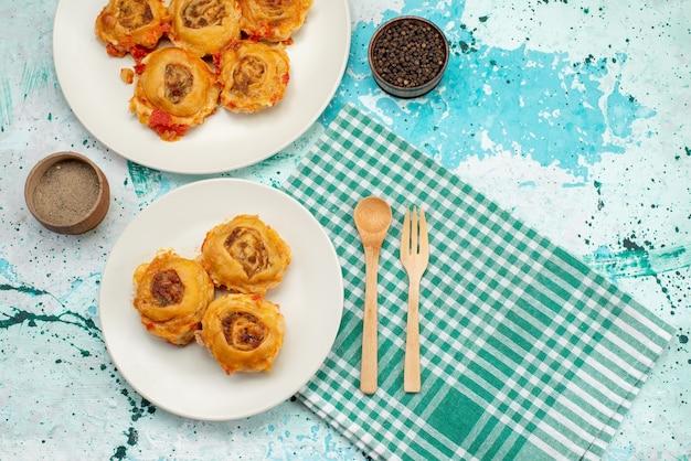 Вид сверху приготовленное тесто с фаршем внутри тарелок на ярко-синем Бесплатные Фотографии
