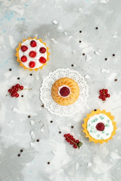 トップの遠景小さなdケーキとクリームとさまざまな果物が軽い表面砂糖甘い上に分離されて 無料写真