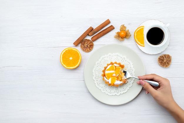 ライトデスク上のコーヒーとシナモン、フルーツケーキビスケットスイートシュガーと一緒にクリームとスライスしたオレンジと小さなケーキのトップ遠景 無料写真