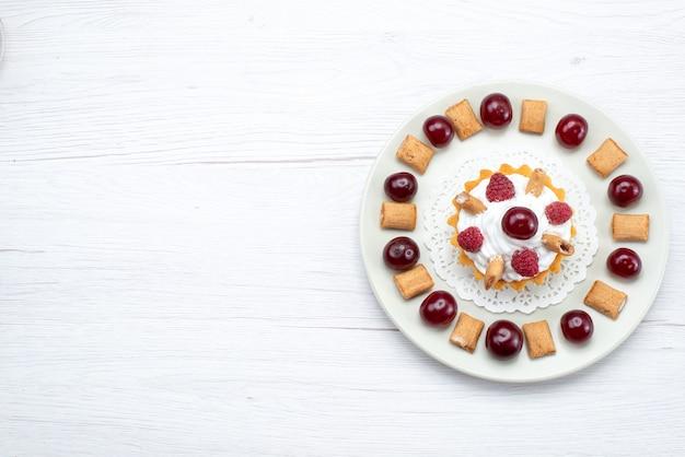 Вид сверху на маленький кремовый торт с малиной и маленьким печеньем на белом фруктовом пироге, сладко-ягодный крем-вишня Бесплатные Фотографии