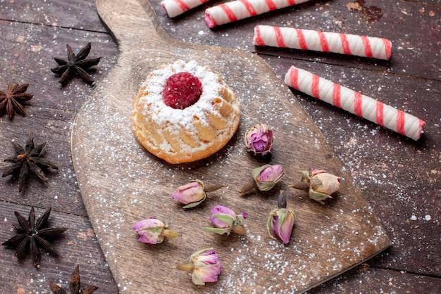 Вид сверху на маленький сливочный торт с малиной вместе с розовыми леденцами на коричневом деревянном, сладком сахарном торте Бесплатные Фотографии