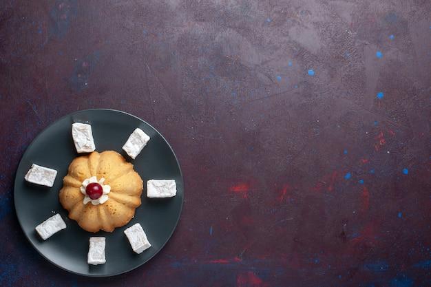 어두운 표면에 접시 안에 케이크와 함께 최고 먼보기 설탕 가루 사탕 맛있는 누가 무료 사진