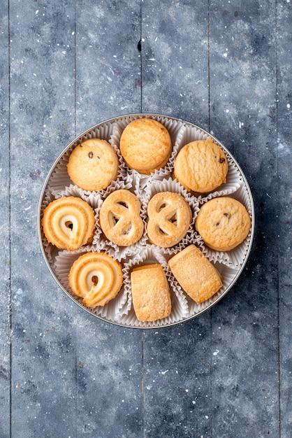 Вид сверху сладкое вкусное печенье, разное, сформированное внутри круглой упаковки на сером столе, сахарное сладкое печенье, печенье Бесплатные Фотографии