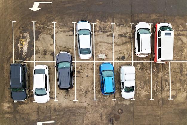슈퍼마켓의 주차장이나 판매 자동차 딜러 시장에서 많은 자동차의 공중보기를 하향식으로하십시오. 프리미엄 사진