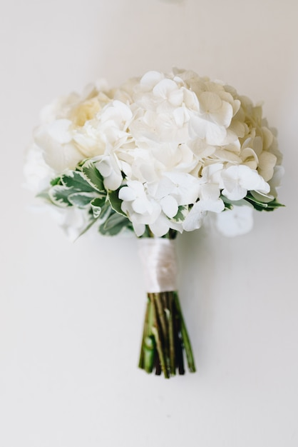 A top-down picture of minimalistic wedding bouquet of white hydrangea Premium Photo