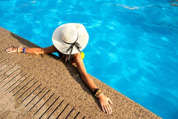 スイミングプールで休んでいる黄色い麦わら帽子をかぶっている若い女性のトップダウンビュー。 Premium写真