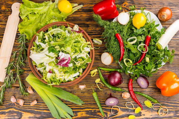 Top down view of rosemary, lettuce, leek, onion, peppers, lemon and other delicious ingredients on wooden table Premium Photo