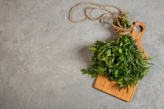 Top  fresh herbs on wooden cutting board on grey Free Photo