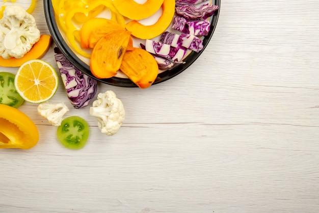 Metà superiore vista tagliare frutta e verdura zucca cachi cavolo rosso limone pomodori verdi sulla piastra nera sul tavolo con copia posto stock photo Foto Gratuite