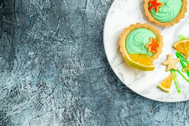 Metà superiore vista piccole crostate con crema pasticcera verde e fetta di limone sul piatto su spazio libero superficie scura Foto Gratuite