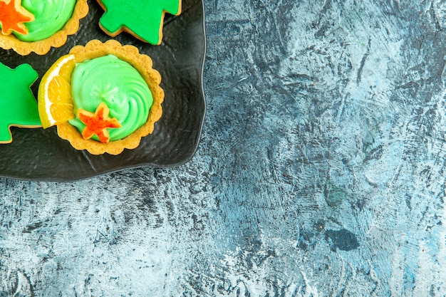복사 공간이 회색 표면에 검은 접시에 녹색 과자 크림 크리스마스 트리 비스킷으로 상위 절반보기 작은 타르트 무료 사진