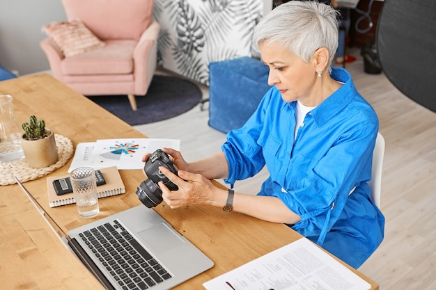 Top high angle view of stylish middle aged female photographer sitting at her workplace with open laptop, holding dslr camera selecting best shots for retouch, having focused concentrated expression Free Photo