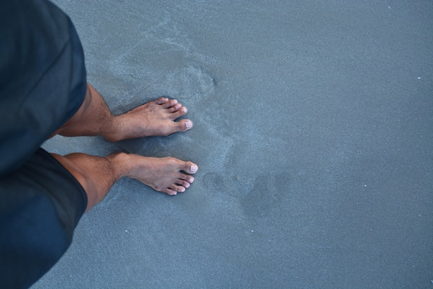 The top of man feet with no shoe on the sand Premium Photo