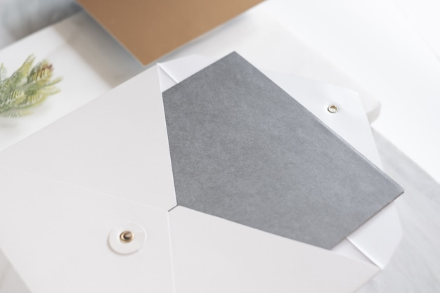 Top perspective view of blank grey card in white envelop with pine leaf on marble table Premium Photo