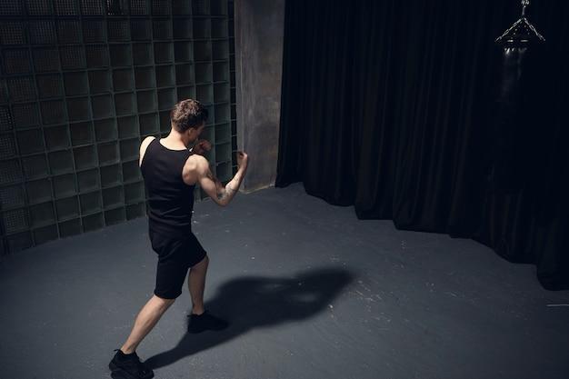 Vista posteriore superiore del giovane atletico abete con braccia muscolose che indossa abiti neri mentre boxe, pugni il nemico invisibile, in piedi isolato in camera oscura, gettando ombra sul pavimento di cemento grigio Foto Gratuite