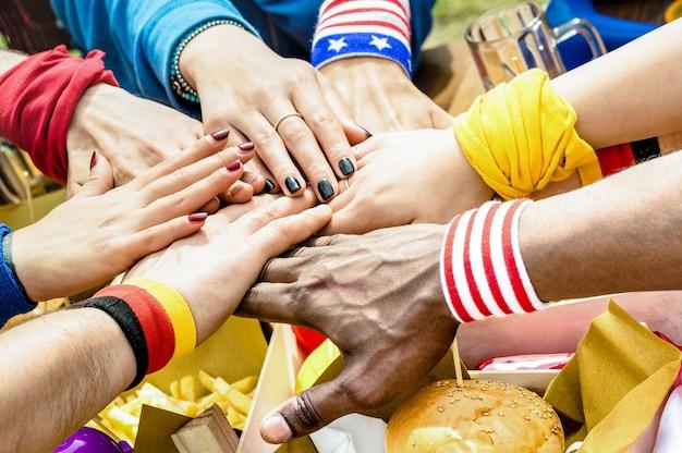 屋台の食べ物を共有するサッカーサポーターの友人の多民族の手の上面図 Premium写真