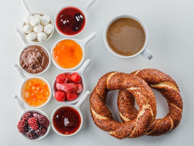 상위 뷰 잼, 라즈베리, 설탕, 컵에 초콜릿, 흰색 표면에 터키 베이글과 커피 한 잔 무료 사진