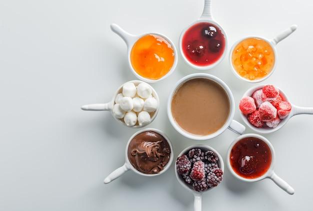 白い表面にジャム、ラズベリー、砂糖、カップのチョコレートとコーヒーのカップを平面図します。 無料写真