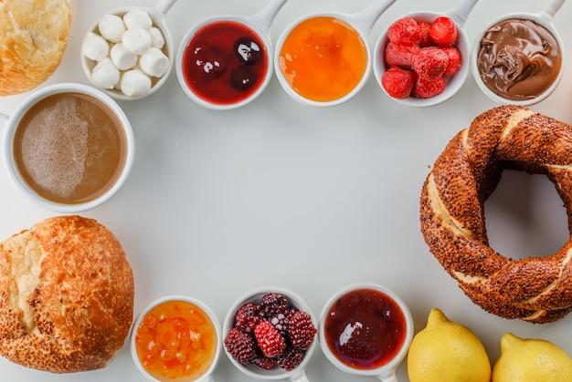 白い表面にジャム、ラズベリー、砂糖、カップのチョコレート、トルコのベーグル、パン、レモンとコーヒーのカップを平面図します。 無料写真