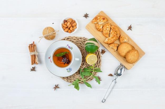 Вид сверху чашка чая, цитрусовые и листья мяты на круглой подставке с печеньем на разделочной доске Бесплатные Фотографии