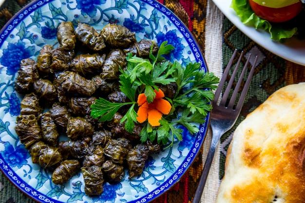 Вид сверху традиционное азербайджанское блюдо мясо долма в виноградных листьях с петрушкой и морковью Бесплатные Фотографии
