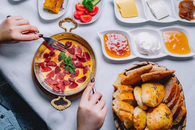 トップビューパンのバスケットとフライパンでソーセージと朝食のオムレツを持つ女性 無料写真
