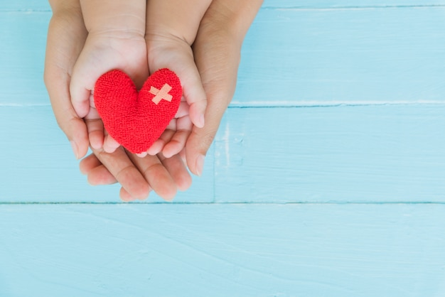 Top view of adult and child holding red heart in hands, happy family relationships Premium Photo