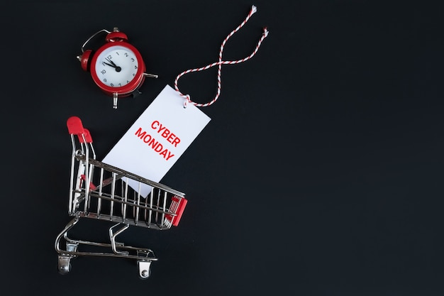 Top view alarm clock and shopping cart with cyber monday sticker on a black . time management, online shopping . Premium Photo