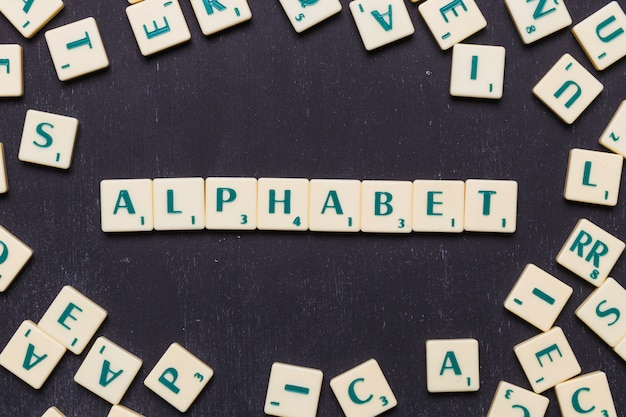 Top view of alphabet text with scrabble letters over black backdrop Free Photo