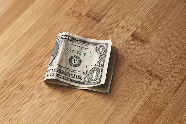 Top view of an american dollar bill on a wooden surface Free Photo
