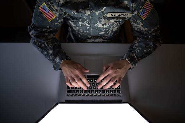 Vista dall'alto del soldato americano in uniforme militare che digita sul computer Foto Gratuite