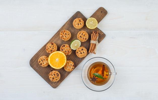 Вид сверху апельсин, лайм, печенье и корица на разделочной доске с чашкой чая на белой поверхности Бесплатные Фотографии