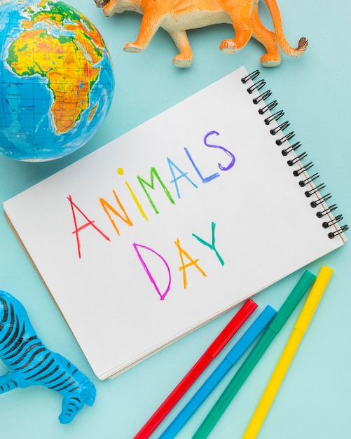 Top view of animal figurines with planet earth and colorful writing on notebook for animal day Free Photo