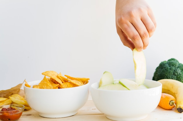 Top view apple bowl vs nachos bowl Free Photo