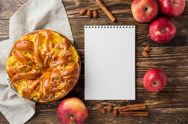 Top view apple pie and fruit surrounding empty note pad Free Photo