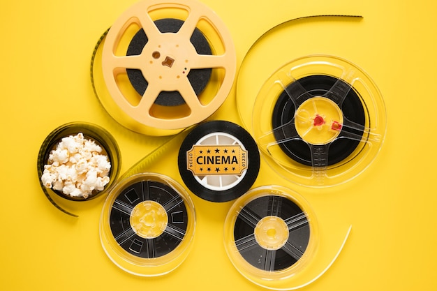 Top view arrangement of cinema elements on yellow background Free Photo